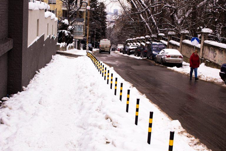 Лозенец, ул. Теодоси Търновски, между оградите на новото посолство на Китай и правителствената резиденция. Улицата е почистена, тротоарът не. Пешеходецът избира пътното платно.